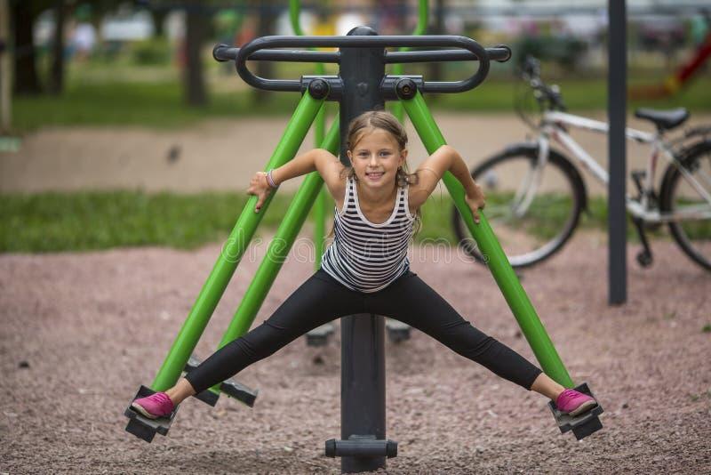 Petite fille mignonne faisant l'étirage sur le terrain de jeu sport images libres de droits
