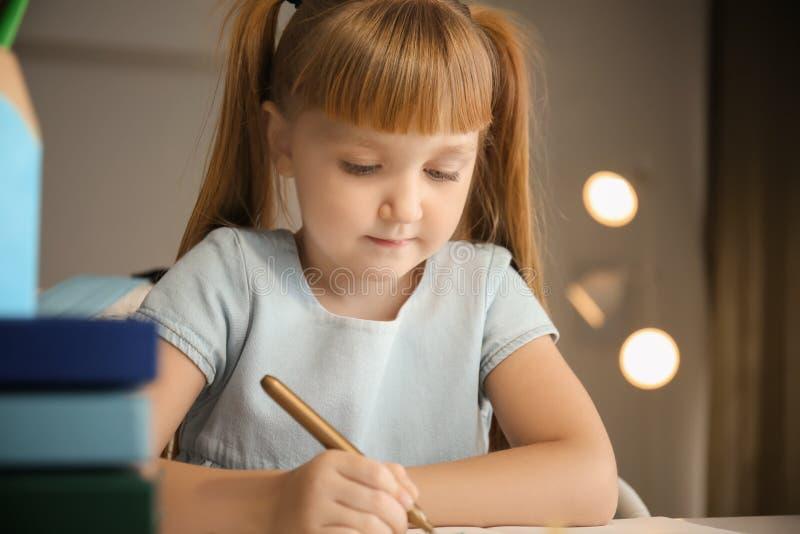 Petite fille mignonne faisant ses leçons à la maison photo stock