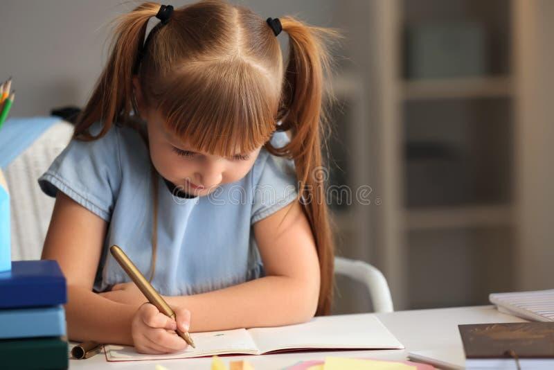 Petite fille mignonne faisant ses leçons à la maison images libres de droits