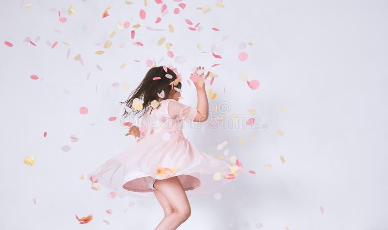 Petite fille mignonne gaie portant la robe rose à Tulle avec la danse de couronne de princesse sur la surprise de confettis sur l photos stock