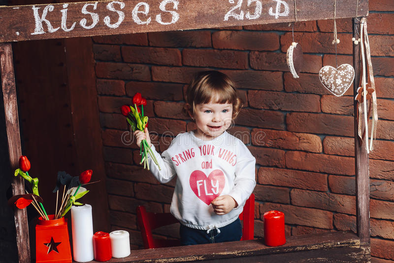 Petite fille mignonne heureuse avec des fleurs dans des mains à la maison photos libres de droits
