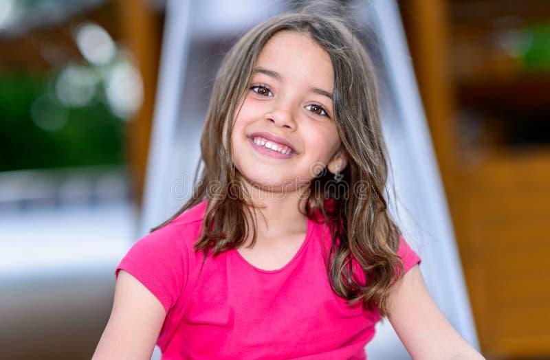 Petite fille mignonne heureuse dans le terrain de jeu image stock