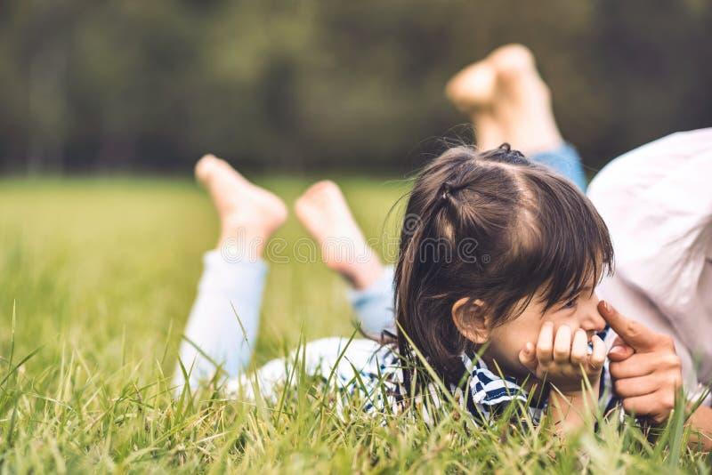 Petite fille mignonne heureuse se trouvant sur l'herbe verte jouant dehors avec sa maman La mère et la fille ont l'extérieur et l image stock
