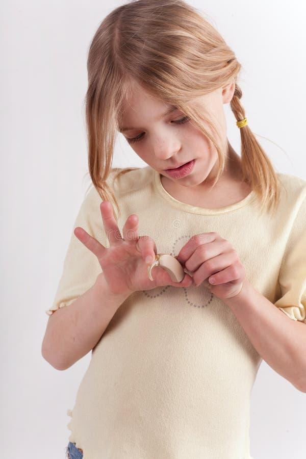 Petite fille mignonne jouant à une prothèse auditive images stock