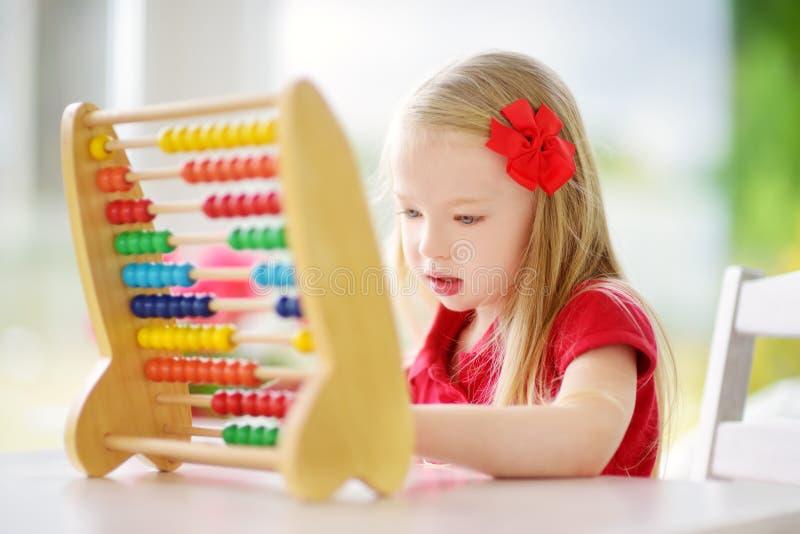 Petite fille mignonne jouant avec l'abaque à la maison Enfant futé apprenant à compter photos stock