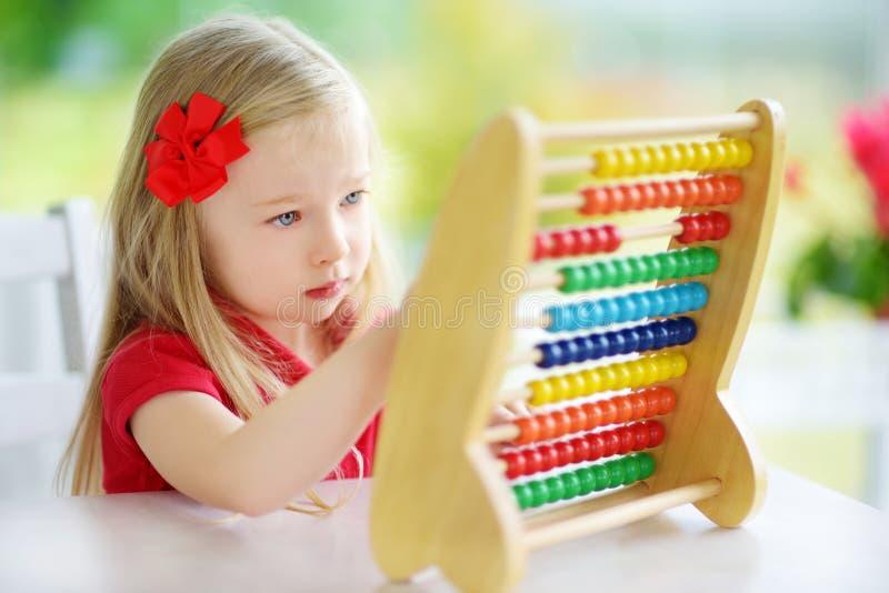 Petite fille mignonne jouant avec l'abaque à la maison Enfant futé apprenant à compter images libres de droits