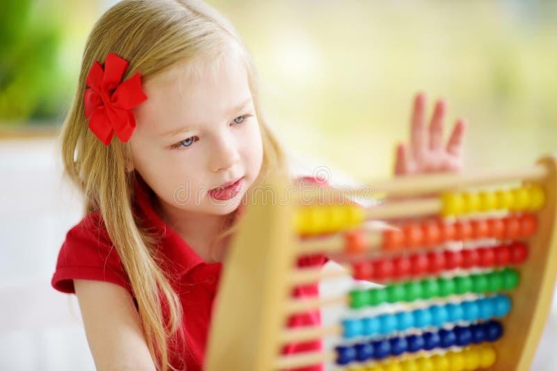 Petite fille mignonne jouant avec l'abaque à la maison Enfant futé apprenant à compter image stock