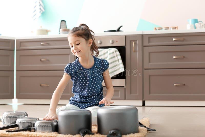 Petite fille mignonne jouant avec la vaisselle de cuisine comme tambours images stock