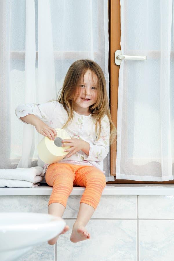 Petite fille mignonne jouant avec le petit pain de papier hygiénique image libre de droits
