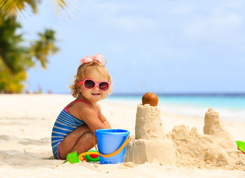 Petite fille mignonne jouant avec le sable sur la plage image stock