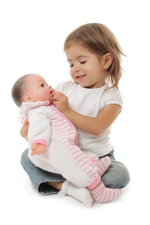 Petite fille mignonne jouant avec sa poupée image libre de droits