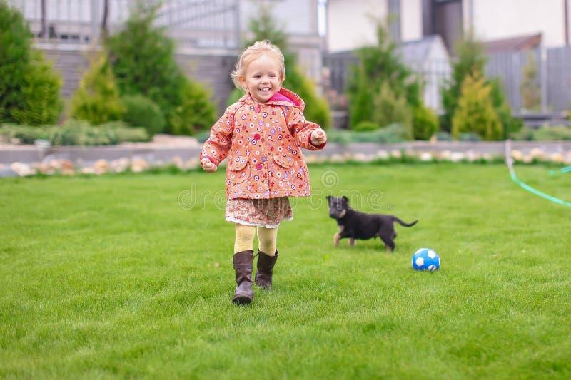 Petite fille mignonne jouant avec son chiot dans la cour images stock