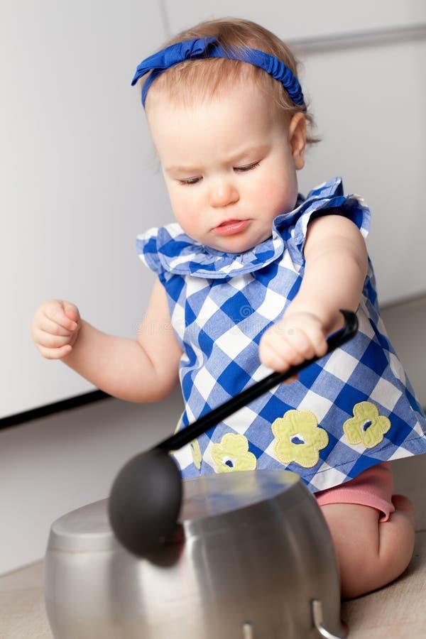 Petite fille mignonne jouant dans la cuisine photo libre de droits