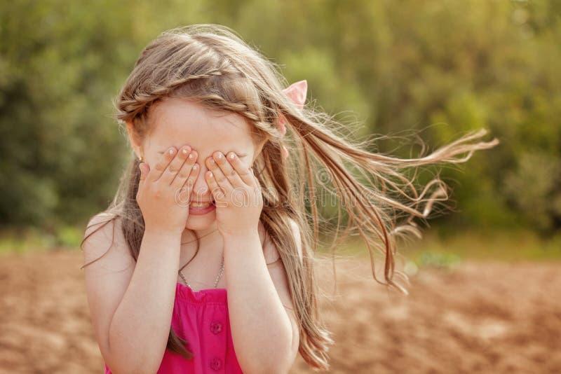 Petite fille mignonne jouant le cache-cache avec l'appareil-photo images libres de droits