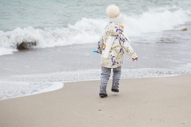 Petite fille mignonne jouant sur la plage sablonneuse Port heureux d'enfant image libre de droits