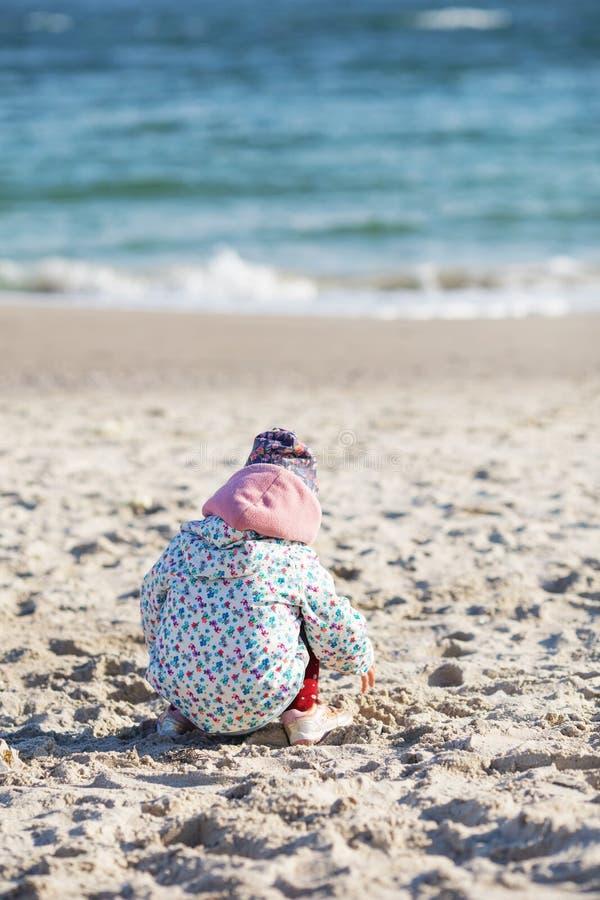 Petite fille mignonne jouant sur la plage sablonneuse Port heureux d'enfant photos stock