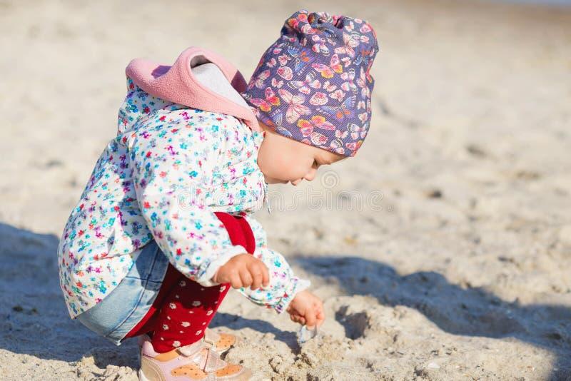 Petite fille mignonne jouant sur la plage sablonneuse Port heureux d'enfant photo stock