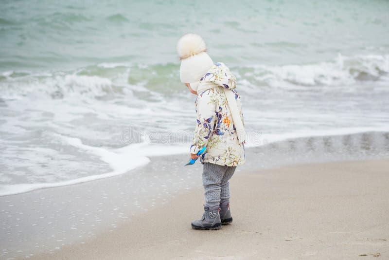 Petite fille mignonne jouant sur la plage sablonneuse Port heureux d'enfant photo libre de droits