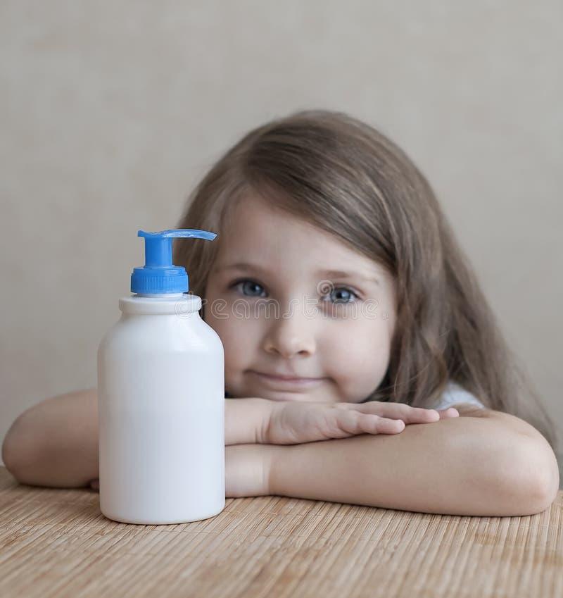 Petite fille mignonne maintenant la bouteille en plastique blanche de shampooing dans ses mains, regardant l'appareil-photo Bain  photos libres de droits