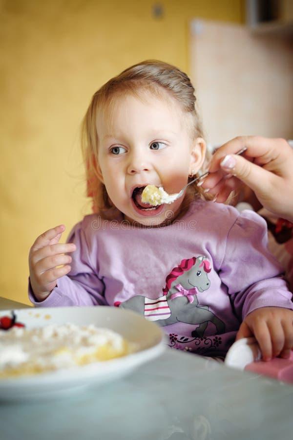 Petite fille mignonne mangeant du gruau image stock