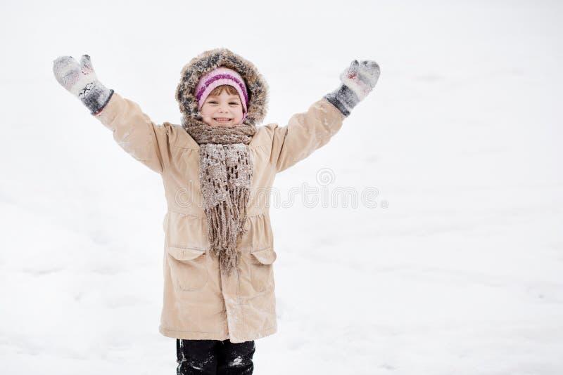 Petite fille mignonne marchant en parc de neige, enfance heureux photo stock