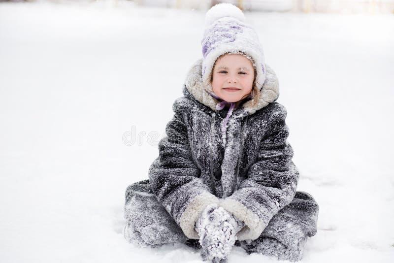 Petite fille mignonne marchant en parc de neige, enfance heureux photos libres de droits