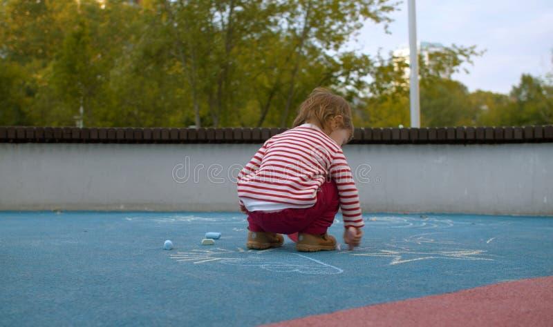 Petite fille mignonne marquant à la craie sur le terrain de jeu photos libres de droits