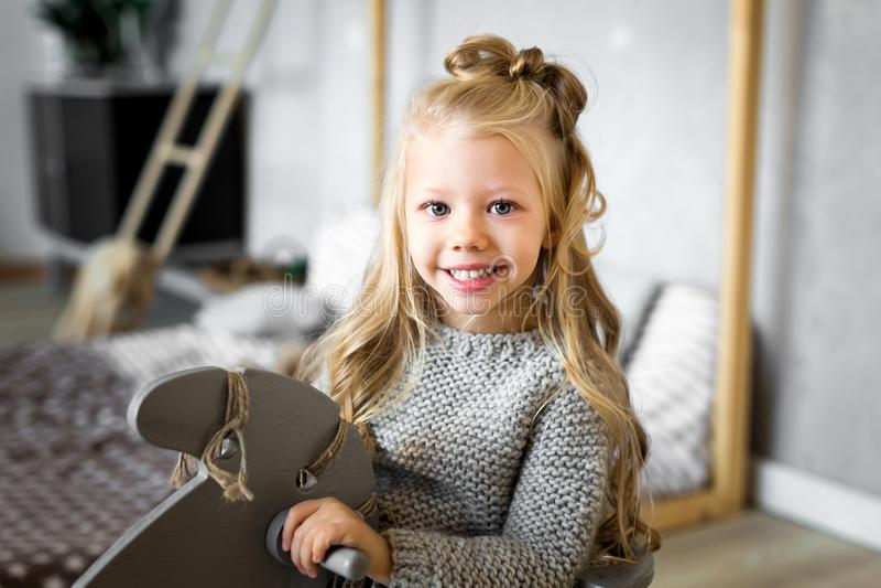 Petite fille mignonne montant un cheval de jouet photographie stock