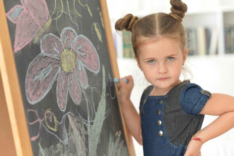 Petite fille mignonne posant près du tableau noir photographie stock