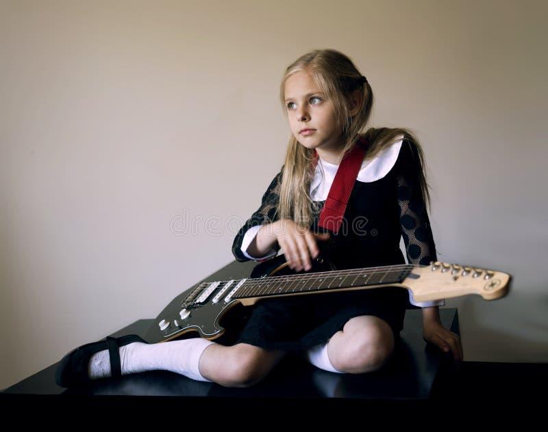 Petite fille mignonne réfléchie avec une guitare se reposant sur le plancher image libre de droits