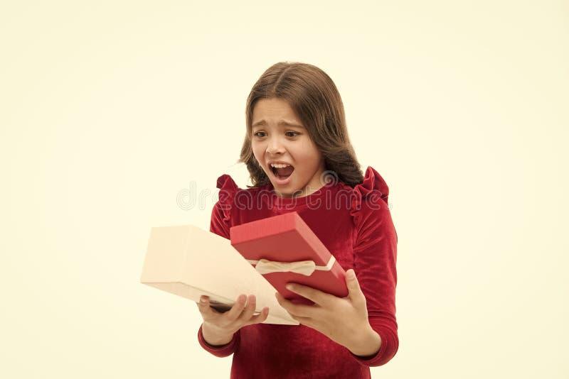 Petite fille mignonne reçoit un cadeau de vacances. A l'intérieur. Les pires jouets et cadeaux de Noël pour les enfants. Petite image libre de droits
