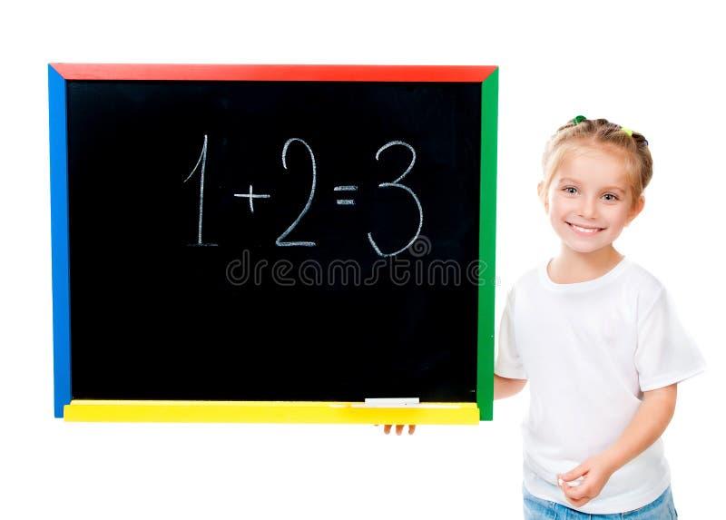 Petite fille mignonne restant le tableau noir proche images libres de droits