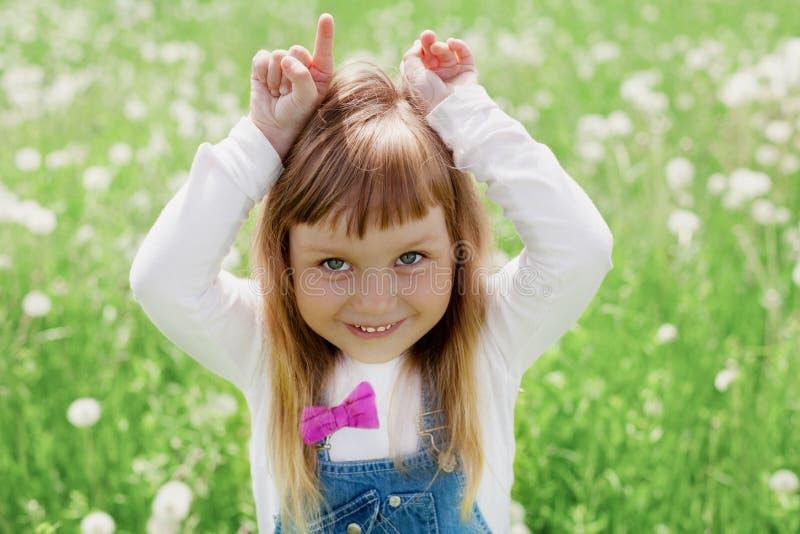 Petite fille mignonne riant et jouant avec ses mains représentant une chèvre sur le pré vert extérieur, concept heureux d'enfance images stock