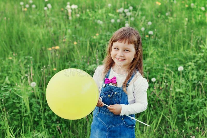 Petite fille mignonne riant et jugeant le ballon de jouet disponible sur le pré vert extérieur, concept heureux d'enfance image stock