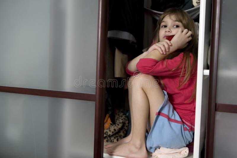 Petite fille mignonne s'asseyant dans la garde-robe photo libre de droits
