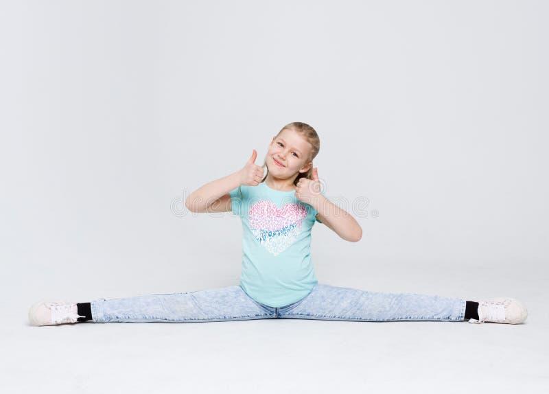 Petite fille mignonne s'asseyant dans les fentes sur le fond blanc de studio image stock
