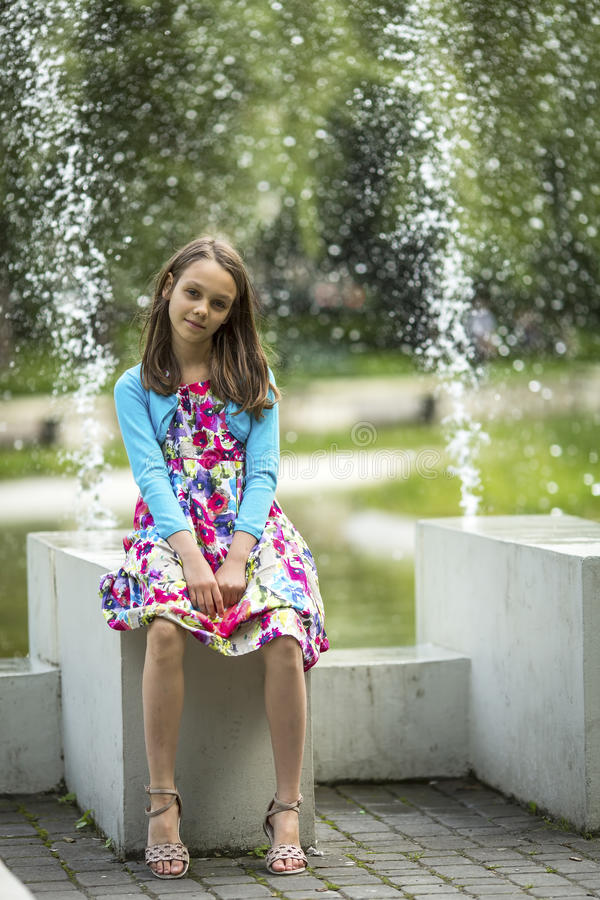 Petite fille mignonne s'asseyant près de la fontaine Marche photos libres de droits