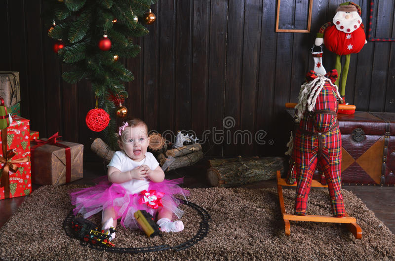 Petite fille mignonne s'asseyant sous l'arbre de Noël Enfant jouant avec un train de jouet image stock