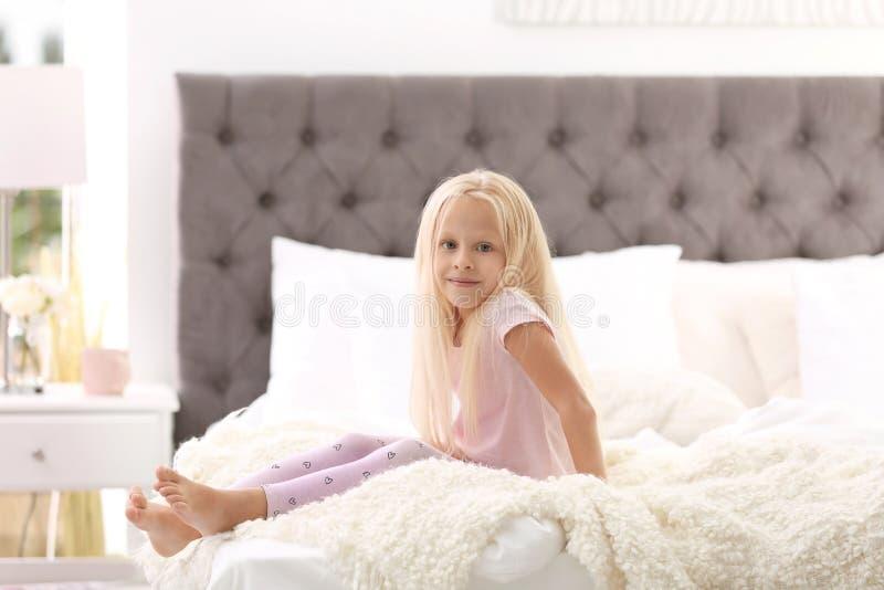 Petite fille mignonne s'asseyant sur le lit avec des oreillers photo libre de droits