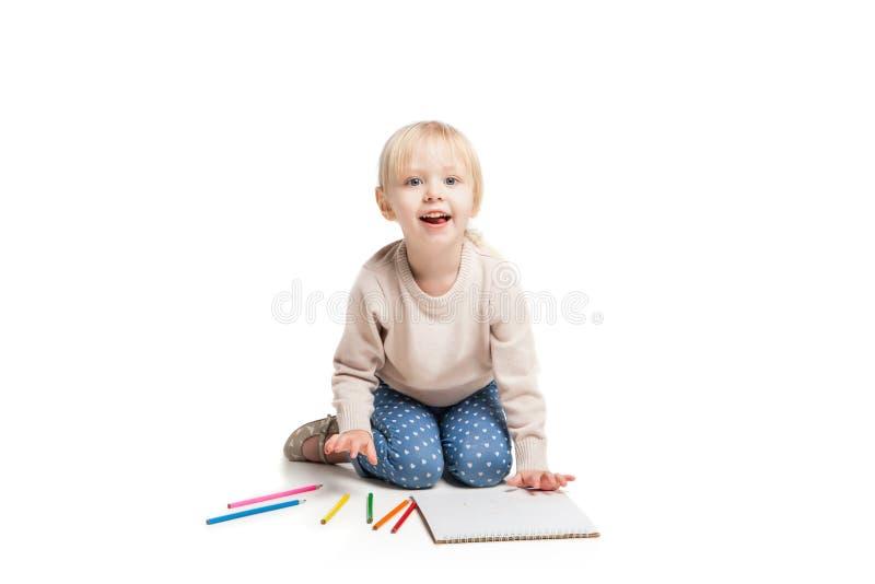 Petite fille mignonne s'asseyant sur le plancher et dessinant avec images libres de droits