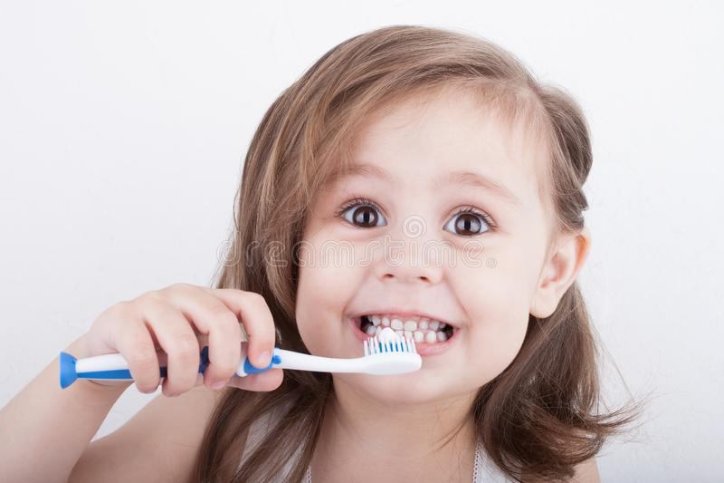 Petite fille mignonne se brossant les dents images libres de droits