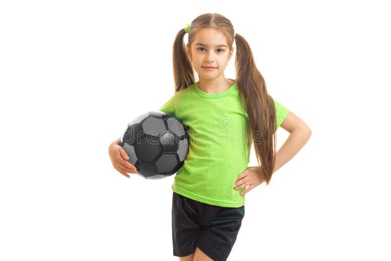 Petite fille mignonne se tenant dans le studio avec la boule et la pose photo libre de droits
