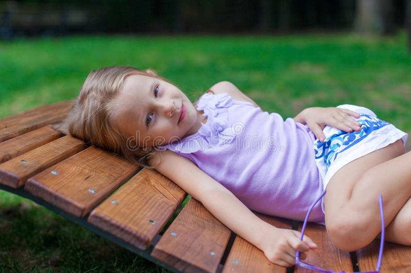 Petite fille mignonne se trouvant sur la chaise en bois extérieure dedans photo stock