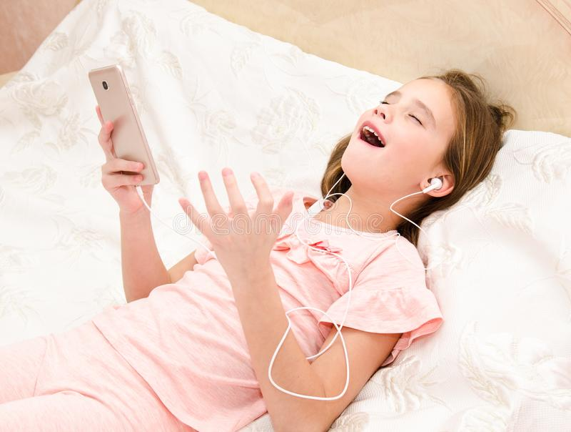 Petite fille mignonne se trouvant sur le lit écoutant la musique et le chant photos libres de droits