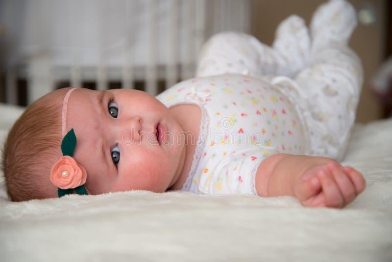 Petite fille mignonne se trouvant sur le lit elle de retour photos stock