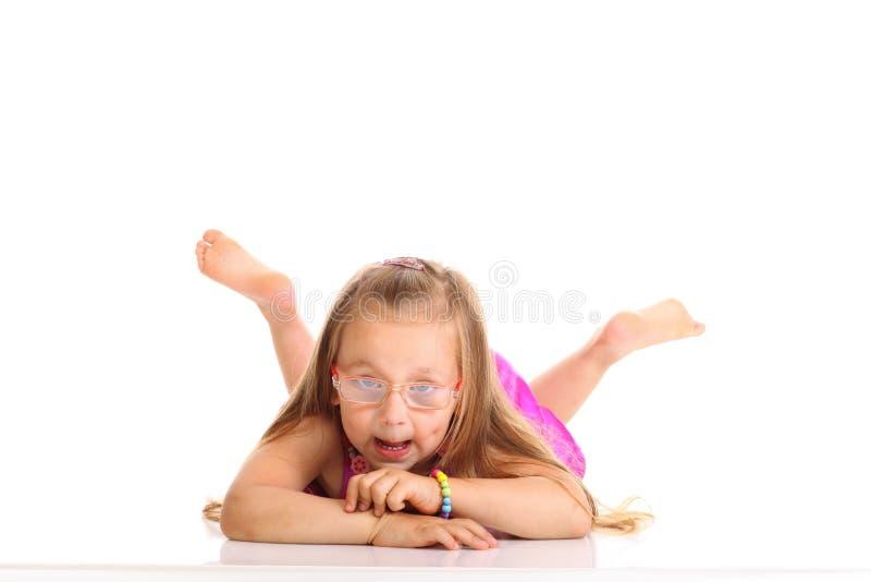 Petite fille mignonne se trouvant sur le plancher faisant l'amusement d'isolement images libres de droits