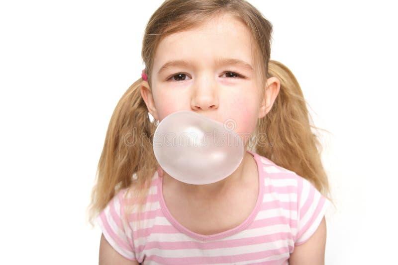 Petite fille mignonne soufflant une bulle de chewing-gum image stock
