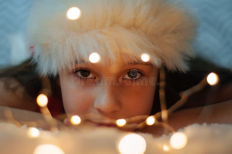 Petite fille mignonne sourit dans un chapeau de santa images libres de droits