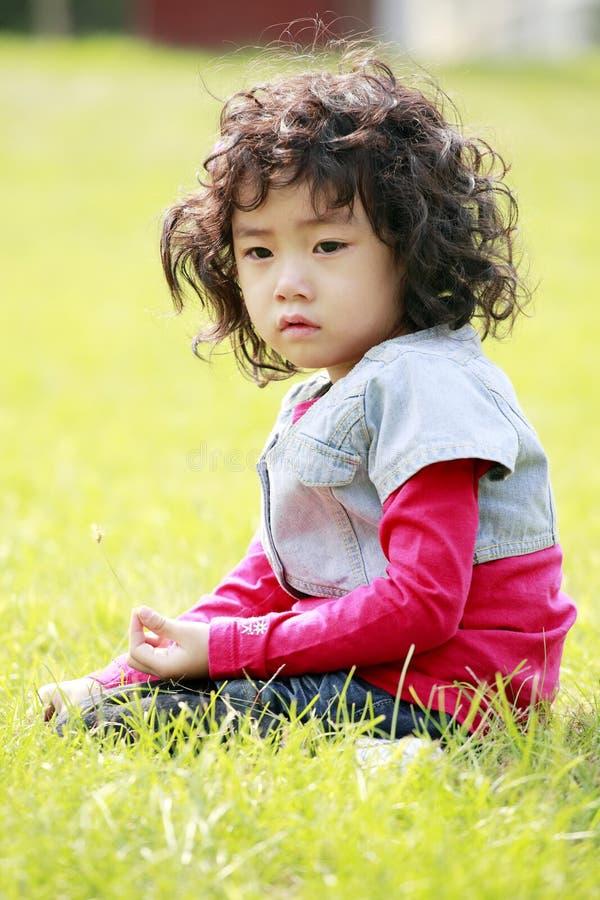 Petite fille mignonne sur l'herbe image stock