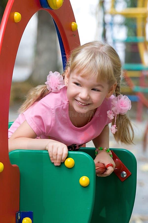 Petite fille mignonne sur la cour de jeu extérieure. image stock
